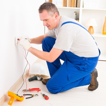 Installer testing the power level of a power socket in a home